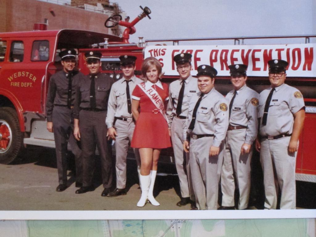 I found this photo from the old days of visiting Kodak during Fire prevention week where we got a tour, appreciation and a photo opp. Here we are in October 1970 with Miss Flame 1970.  Captain Doug is far left with Asst.Chief Al Willmes, Dave Vendel, Chaplain me, Mike Smith, Ed Montgomery and Gene Miller. Engine 102 a 1966 Ford by Young Ford by Young is pictured. Peace Chaplain Bill Michatek.